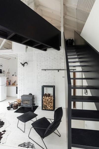 納屋をリノベーションしたロフトハウスのロフトへ上がる階段とその下の暖炉