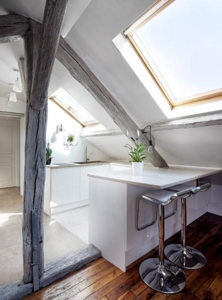 大きな天窓の入った勾配天井の下の明るく開放的なロフトのダイニングキッチン