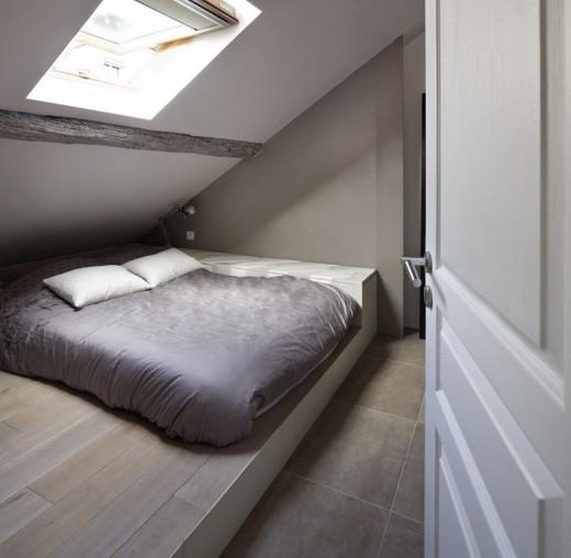 大きな天窓の入った勾配天井の下の包まれ感と開放感のある明るいベッドルーム