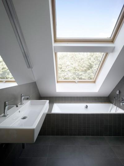 勾配天井の下の大きな天窓が2つあるバスルーム
