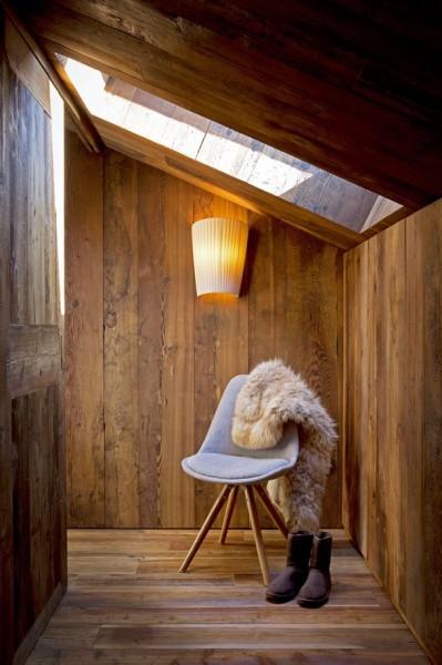 天窓のある低い勾配天井の下のコーナーに座り心地の良さそうな椅子を置いた寛ぎのスペース