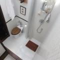 木製のパーツをあしらった白いタイル張りのバスルーム