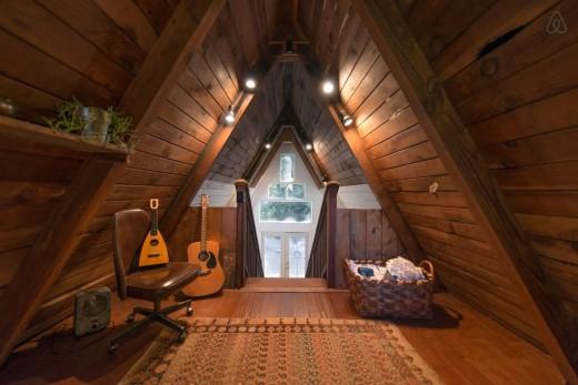森の中に建つコンパクトなAフレームの山小屋 2階のロフトベッドルームから入口側