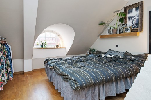 丸い窓のある勾配天井下のベッドルーム2