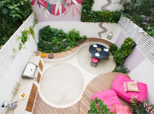 BBQグリルの屋外キッチンとカラフルなソファベッドのあるコンパクトなテラスのアウトドアリビング・ダイニング