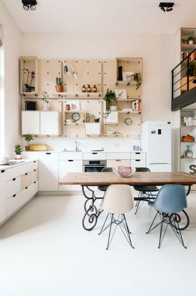 壁面に、有孔ボード的なパネルを用いた大きな可変棚のあるダイニング・キッチン