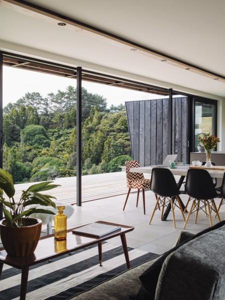 全開口のガラススライドドアと長大なウッドデッキのテラスのある開放的なリビング