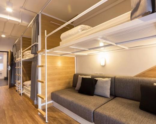タイ バンコクのユースホステルのベッドルームに並ぶ2段ベッドとその下に置かれたソファ