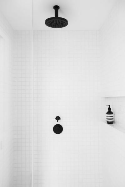 マットなブラックの水栓金物を用いた白いタイル張りのバスルーム2