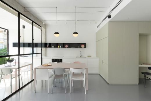 片隅の窓際に小上がり的な1段高い寛ぎスペースのある明るく開放的なリビング・ダイニング・キッチンのダイニングスペース