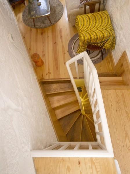 ポルトガル ポルトの中心部に建つ三角形の狭小住宅の最上階のキッチンから階段下を覗く