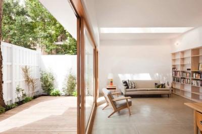 ウッドデッキの中庭に面する、大きな作り付け本棚のあるリビング