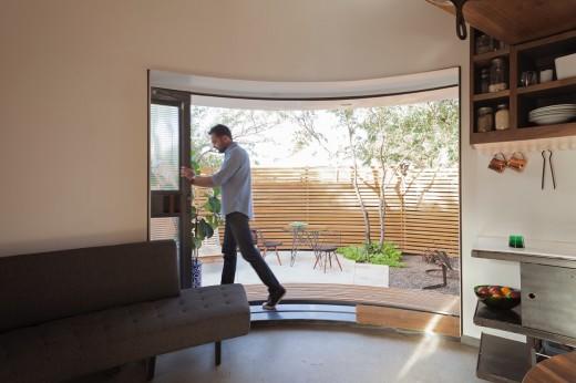 穀物サイロを流用して作った円筒形のコンパクトハウス 庭とリビング・ダイニングの間は2.7m幅の全開口スライドドア