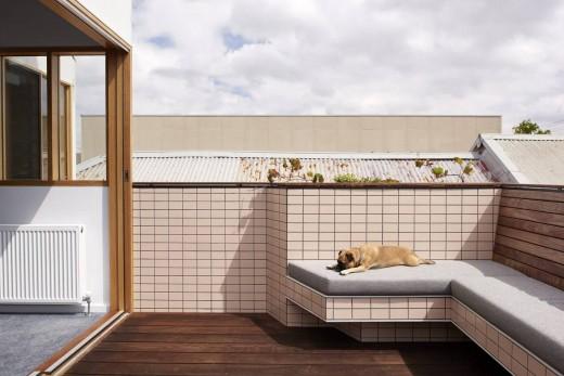 大きなガラスのスライドドアで屋内とつながる、デイベッド的な造作ベンチのあるウッドデッキのバルコニー