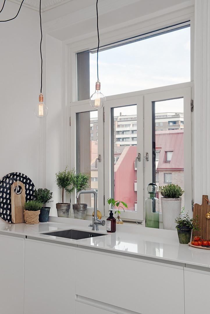 ペンダントランプの吊り下がった大きな窓のある明るいキッチン