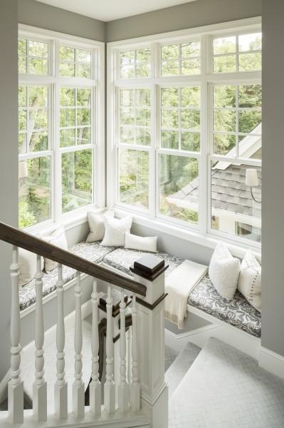 二面の壁全体に上げ下げ窓を埋め込み、壁際にデイベッドを配した、サンルームのような明るく開放的な階段室