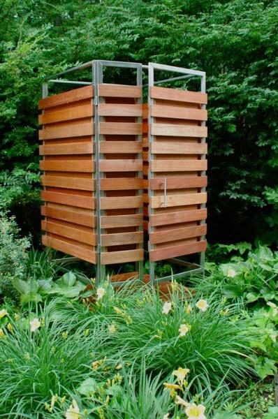 ステンレスフレームと広葉樹の組み合わせで作られた、ユニット化された屋外用シャワーブースを庭に設置