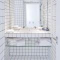 純白のタイルの敷き詰められた透明感のあるバスルーム1