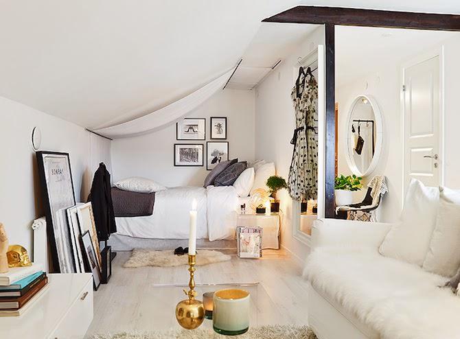 布の張られた斜め天井の下の屋根裏のベッドルーム