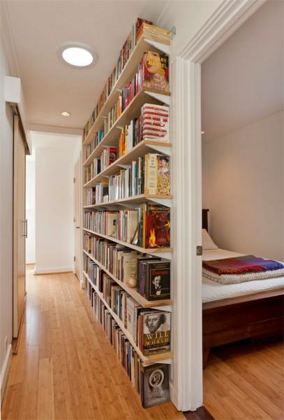 芝生の裏庭のあるコンパクトな平屋の一戸建ての、巨大な造作本棚のある廊下