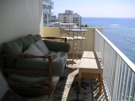 座り心地の良いソファの置かれた、海沿いのペントハウスのベランダの屋外リビングスペース