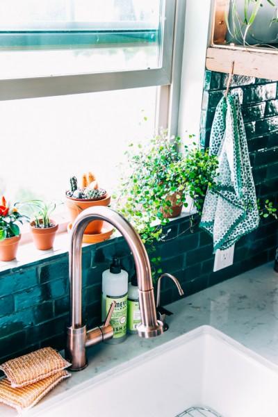 エメラルドグリーンのタイルのキッチンの窓際と観葉植物