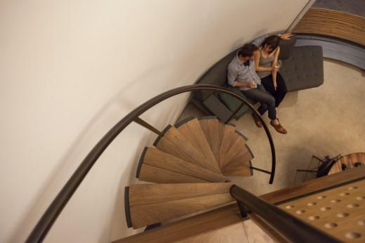 穀物サイロを流用して作った円筒形のコンパクトハウス 2階のベッドルームからリビングを見下ろす 螺旋階段と扇型ソファ