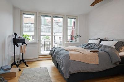 開放的なバルコニー付きのスウェーデンのロフトアパートのベッドルーム