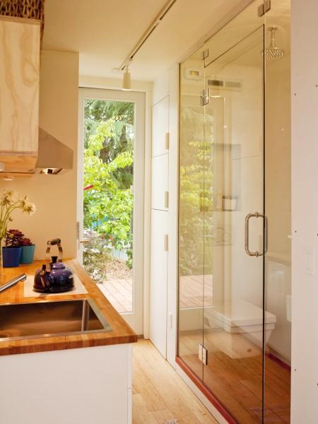 10.7畳のスペースに2つのダブルベッドとリビング、キッチン、バスルームのあるコンテナハウスのキッチンとバスルーム