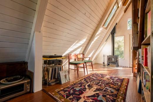 森の中に建つコンパクトなAフレームの山小屋 勾配天井下のスペース 暖炉