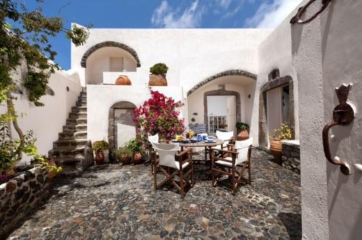 地中海風の白い漆喰で作られたギリシャ サントリーニ島のヴィラの中庭の屋外ダイニングスペース