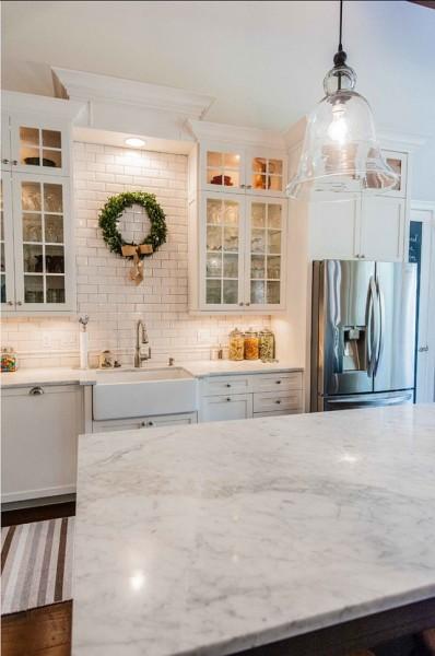 ガラスシェードのペンダントライトとガラス扉のウォールキャビネットのあるキッチン