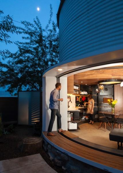 穀物サイロを流用して作った円筒形のコンパクトハウス 庭とリビング・ダイニングの間の全開口スライドドア 夜 庭から