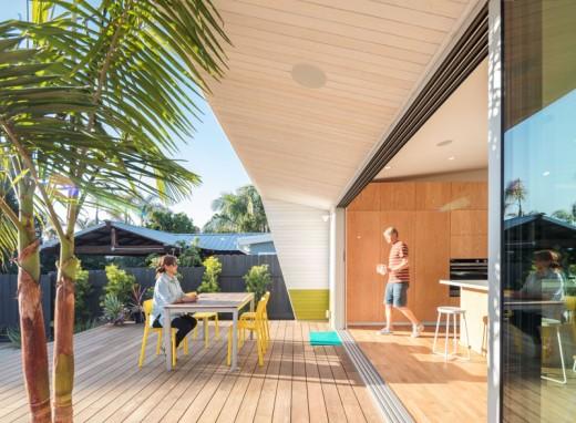 全開口のスライドドアでダイニング・キッチンとシームレスにつながるウッドデッキのテラスの屋外ダイニング