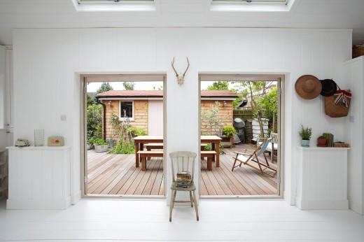 庭に建てられた平屋の多目的スペースの2つ並んだフレンチドアからウッドデッキの屋外ダイニングをのぞむ