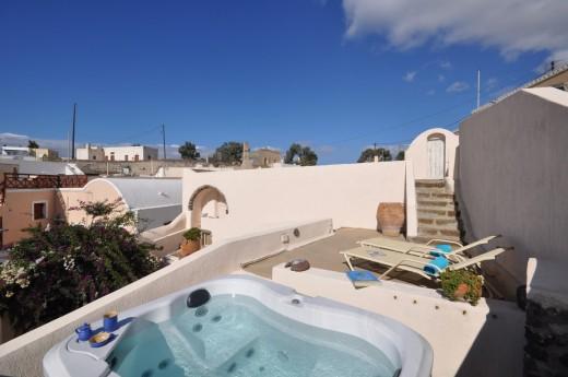 地中海風の白い漆喰で作られたギリシャ サントリーニ島のヴィラの屋上の屋外ダイニング&スパスペース スパを上から