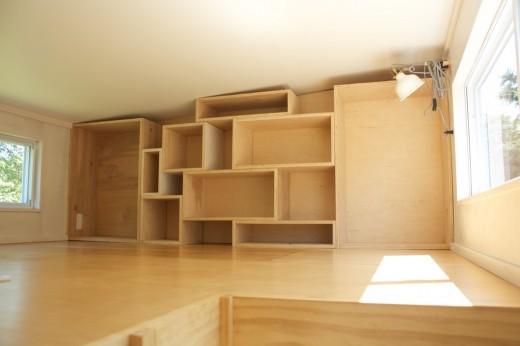 ロフトの上の天井の低い多目的スペースの壁面収納