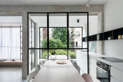 片隅の窓際に小上がり的な1段高い寛ぎスペースのある明るく開放的なリビング・ダイニング・キッチンのダイニングとその向こうのテラス