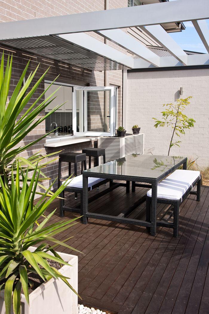 キッチンと大きな窓でつながるパーゴラのあるテラスの屋外ダイニング