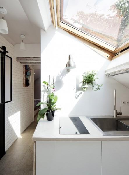 大きな天窓の入った勾配天井の下の明るく開放的なロフトのキッチン