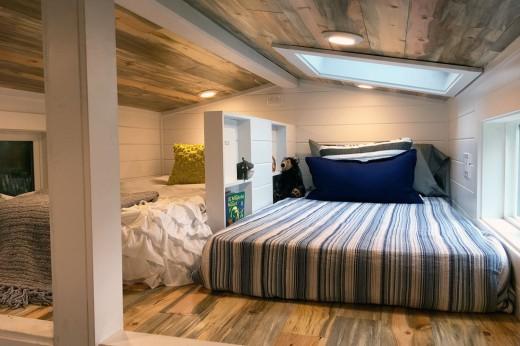 ロフトの天窓付きの低い勾配天井の下のベッドルームを低い棚で区切って2部屋に