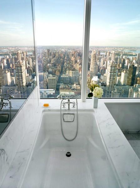 窓の外に向かって体を横たえるバスタブのある全面ガラス張りのバスルーム