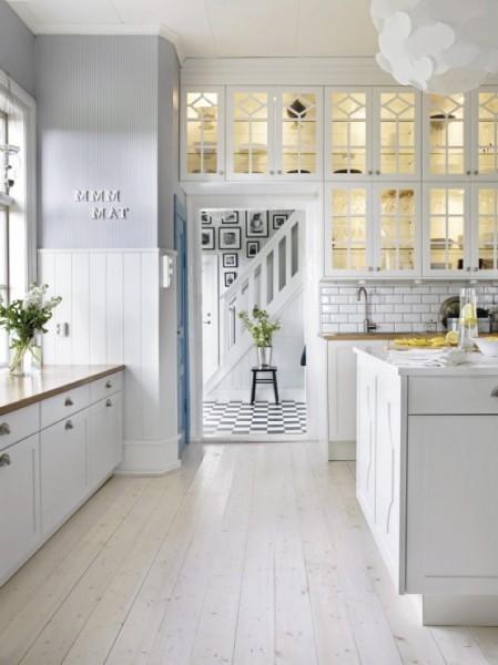 ライトの埋め込まれた大きなガラス戸棚のあるキッチン