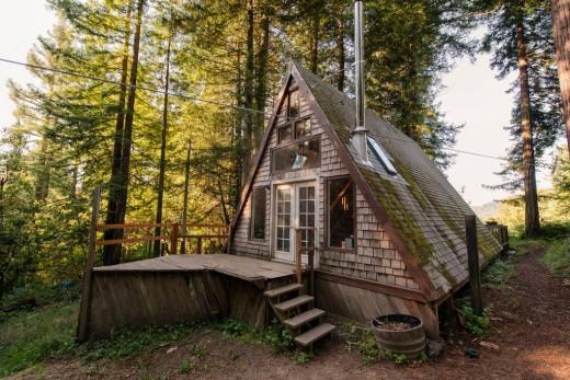 森の中に建つコンパクトなAフレームの山小屋の外観 昼間