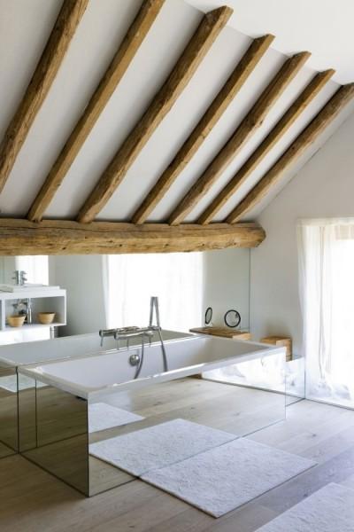 低い掃き出し窓と大きな鏡のあるロフトのバスルーム