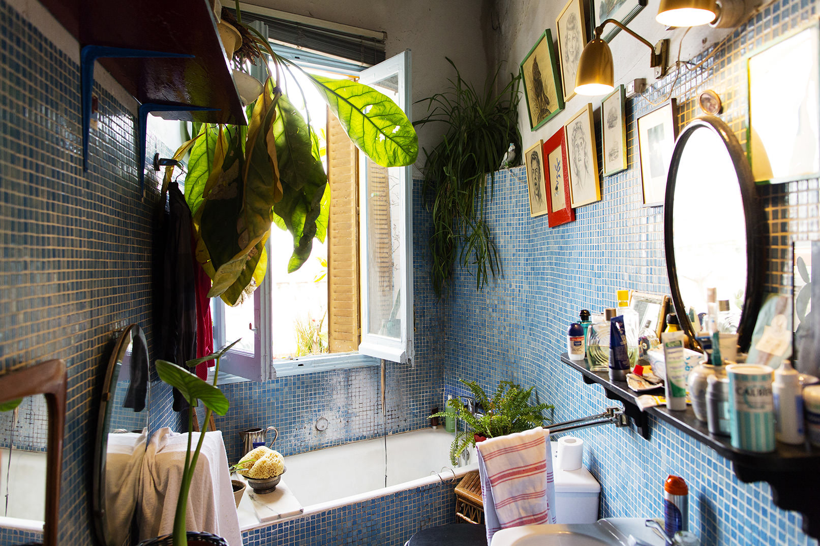 マドリッドのデザイナーの家の屋外のような明るブルーのタイル張りの明るいバスルーム1