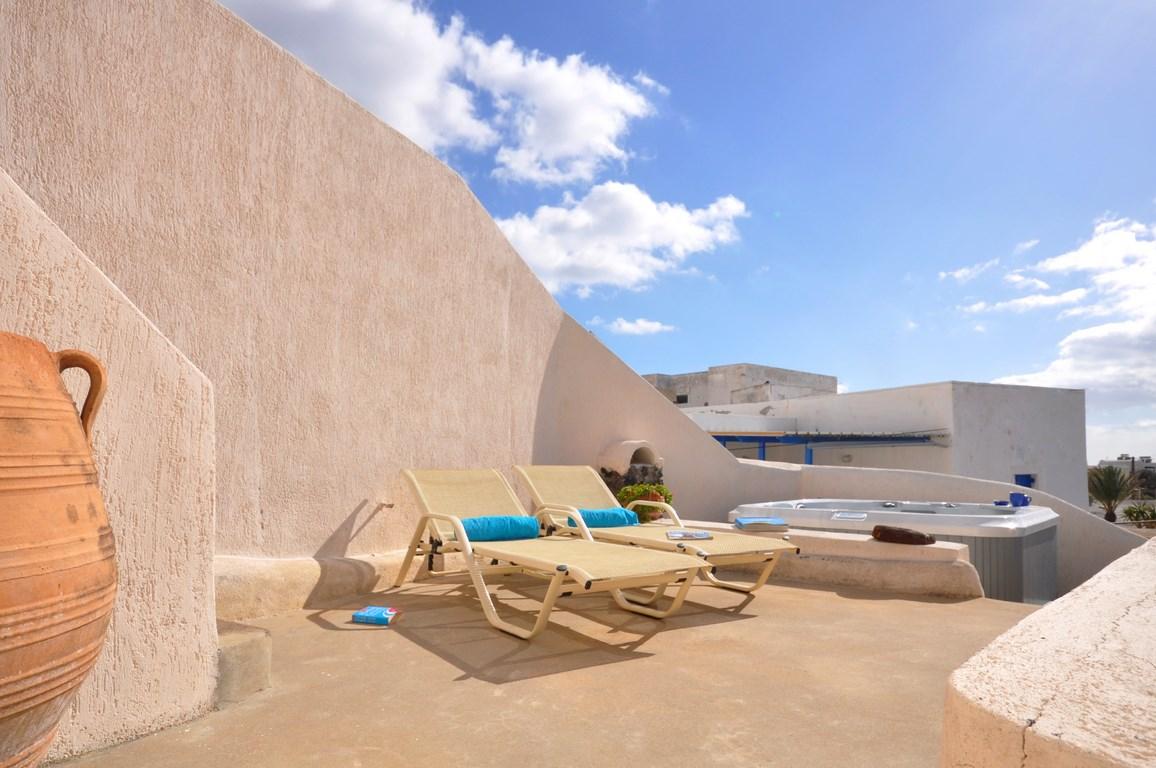 地中海風の白い漆喰で作られたギリシャ サントリーニ島のヴィラの屋上の屋外ダイニング&スパスペース