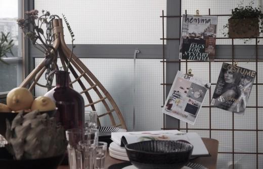 しっかりとしたテーブルと椅子のセットのある広めのベランダの屋外ダイニングの壁面のワイヤーを使った収納