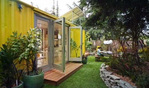 10.7畳のスペースに2つのダブルベッドとリビング、キッチン、バスルームのあるコンテナハウスの裏庭側