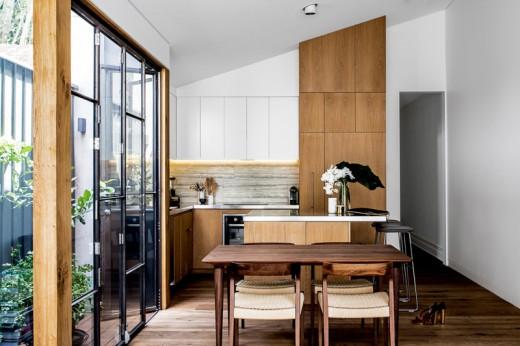隣に温室のようなコンパクトなウッドデッキのテラスのある開放的なダイニング・キッチン